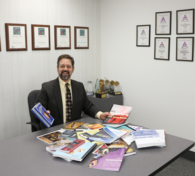 Copresco President Steve Johnson shows off clients' digital books and publications.